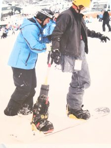 Two individuals are facing the same direction with the coach's hands on the athlete's back. The athlete is riding a snowboard with one leg strapped in and o an outrigger held by the athlete's right arm strapped into the binding.