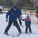 A coach in a blue ski jacket, whose skis are positioned in a wedge, holds the hand of a child skier whose skis are parallel.