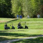 Two golf carts are parked in the foreground, and further back four individuals are standing on the green.